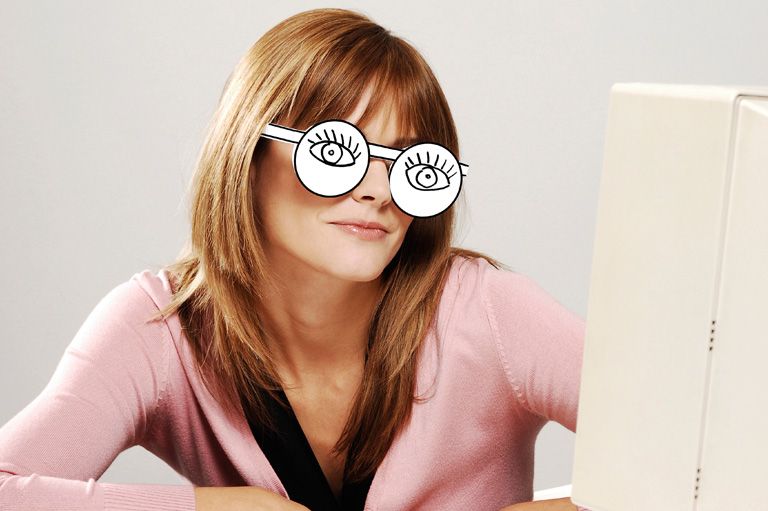 Buy YouTube subscribers and views - bored woman wearing cardboard cutout spectacles at the computer
